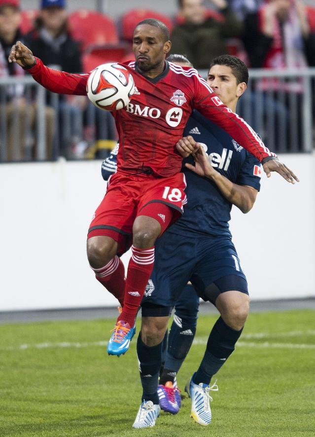 Toronto FC forward Jermain Defoe, left, battles for the ball against Vancouver Whitecaps defender Johnny Leveron, right, during first half semi-final Amway Canadian Championship soccer action in Toronto on Wednesday, May 7, 2014. (AP Photo/The Canadian Press, Nathan Denette)