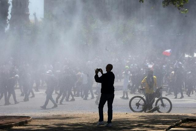 A passerby photographs protests in Santiago, Chile (AFP Photo/CLAUDIO REYES)