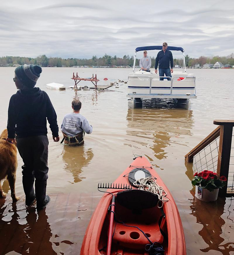 A man in a pontoon boat rescues the Lackey and Schulz families from their lakefront homes. (Courtesy of Sarah Schulz)