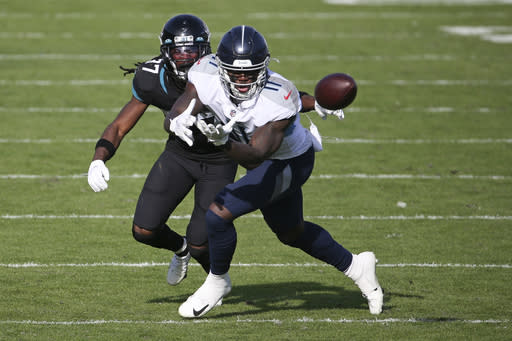 Tennessee Titans wide receiver A.J. Brown, right, makes a reception in front of Jacksonville Jaguars cornerback Tre Herndon (37) during the second half of an NFL football game, Sunday, Dec. 13, 2020, in Jacksonville, Fla. (AP Photo/Stephen B. Morton)