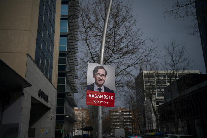 A poster with a photo of Catalan Socialist Party (PSC) candidate in the upcoming Catalan elections Salvador Illa, hangs on a streetlight next to the party headquarter in Barcelona, Spain, Monday, Feb. 8, 2021. A former health minister of Spain hopes to become a quiet political disruptor in the country's Catalonia region when voters go to the polls next weekend. (AP Photo/Emilio Morenatti)