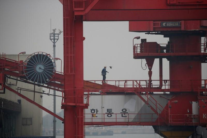An employee walks on a crane at a container terminal at Incheon port in Incheon