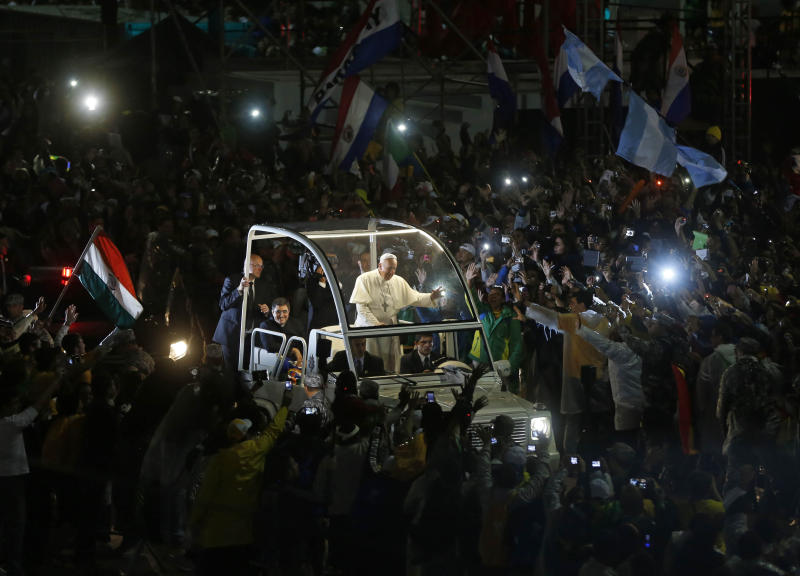 """In this July 25, 2013 file photo, Pope Francis waves from his popemobile as he makes his way through the crowds lining the Copacabana beachfront in Rio de Janeiro, Brazil. Since his March 2013 election, Pope Francis has started a revolution in the Roman Catholic church that charmed millions and the mainstream media, as he goes about doing what he was elected to do: reform not just the dysfunctional Vatican bureaucracy but the church itself, using his own persona and personal history as a model. But the enthusiasm isn't necessarily shared across the board. Traditionalist Catholics — so coddled by Benedict XVI in his pursuit to reach out to Catholics attached to the old Latin Mass and opposed to the modernizing reforms of the Second Vatican Council — greeted Francis' election with concern and now have had their worst fears realized. Francis has spoken out both publicly and privately against such """"restoratist groups"""" whom he accused of being naval-gazing retrogrades out of touch with the evangelizing mission of the church in the 21st century. (AP Photo/Enric Marti)"""