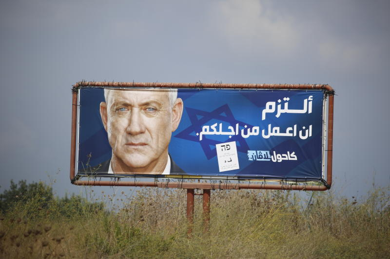 """An election campaign billboard shows the Blue and White party leader Benny Gantz, in the Arab town of Baqa al-Gharbiyye, northern Israel, Monday, Sept. 16, 2019. The Arab writing says, """" I commit to work for you.""""  Israel will hold general elections on Tuesday. (AP Photo/Ariel Schalit)"""