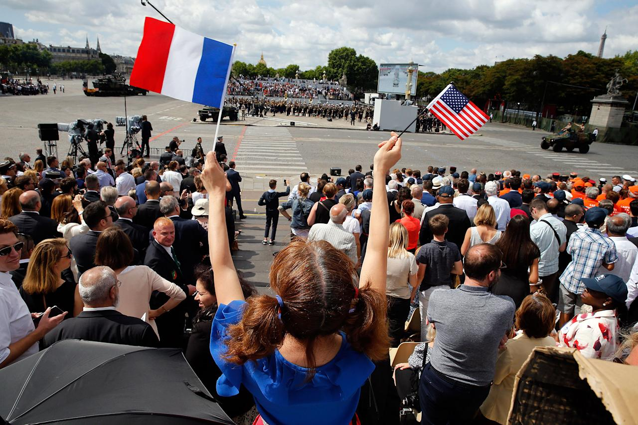 <p>A woman holds a French flag and an American flag during the traditional Bastille day military parade on the Champs-Elysees on July 14, 2017 in Paris France. Bastille Day, the French National day commemorates this year the 100th anniversary of the entry of the United States of America into World War I. (Photo: Thierry Chesnot/Getty Images) </p>