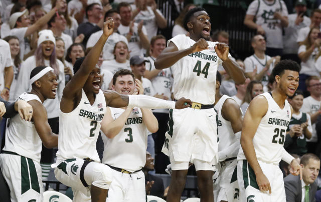From left, Michigan State guards Cassius Winston (5), Rocket Watts Jr. (2), Foster Loyer (3), and forwards Gabe Brown (44) and Malik Hall (25) react on the bench as guard Steven Izzo scores his first point on a free throw during the second half of an NCAA college exhibition basketball game against Albion, Tuesday, Oct. 29, 2019, in East Lansing, Mich. Izzo is a walk-on and son of head coach Tom Izzo. (AP Photo/Carlos Osorio)