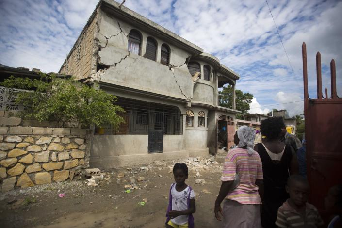 Residents look at a home damaged by a magnitude 5.9 earthquake the night before, in Gros Morne, Haiti, Sunday, Oct. 7, 2018. Emergency teams worked to provide relief in Haiti on Sunday after the quake killed at least 11 people and left dozens injured. ( AP Photo/Dieu Nalio Chery)