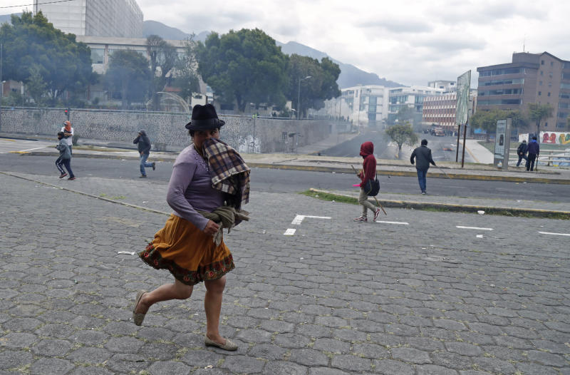 An indigenous anti-government protester runs from tear gas fired by police during clashes near the National Assembly in Quito, Ecuador, Tuesday, Oct. 8, 2019. Anti-government protests, which began when President Lenín Moreno's decision to cut subsidies led to a sharp increase in fuel prices, has persisted for days, and clashes led the president to move his besieged administration out of Quito. (AP Photo/Dolores Ochoa)