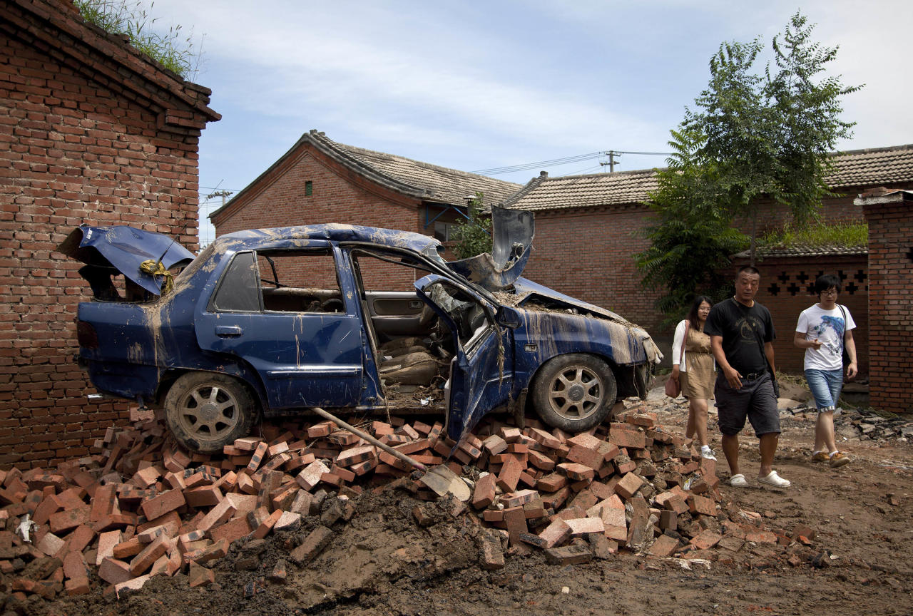 Chinese people walk past a flood damaged vehicle sitting on the bricks at a village in Fangshan district of Beijing, China Monday, July 23, 2012. As China's flood-ravaged capital dealt with the aftermath of the heaviest rain in six decades Monday, including the deaths of 37 people, questions were being raised about whether the city's push for modernization came at the expense of basic infrastructure such as drainage networks. (AP Photo/Andy Wong)