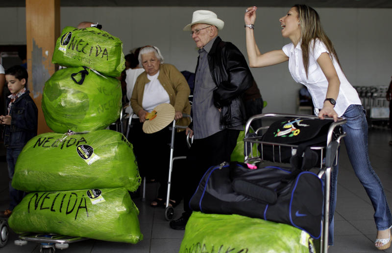"""Cubans who live in the U.S. arrive with packages that read """"Nelida"""" to the Jose Marti International Airport as they arrive to Havana, Cuba, Monday, Sept. 3, 2012. A steep hike in customs duties has taken effect Monday in Cuba, catching some air travelers unaware. Nelida Diaz, center left, says she was shocked when officials charged her $588 at customs. The woman at right is speaking to a person who came to get her at the airport. (AP Photo/Franklin Reyes)"""