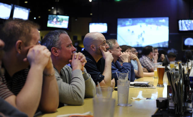 Patrons of a restaurant watch as the United States Men's Olympic Hockey team loses to Canada at the Sochi Olympics, Friday, Feb. 21, 2014 in College Park, Md. (AP Photo/Susan Walsh)