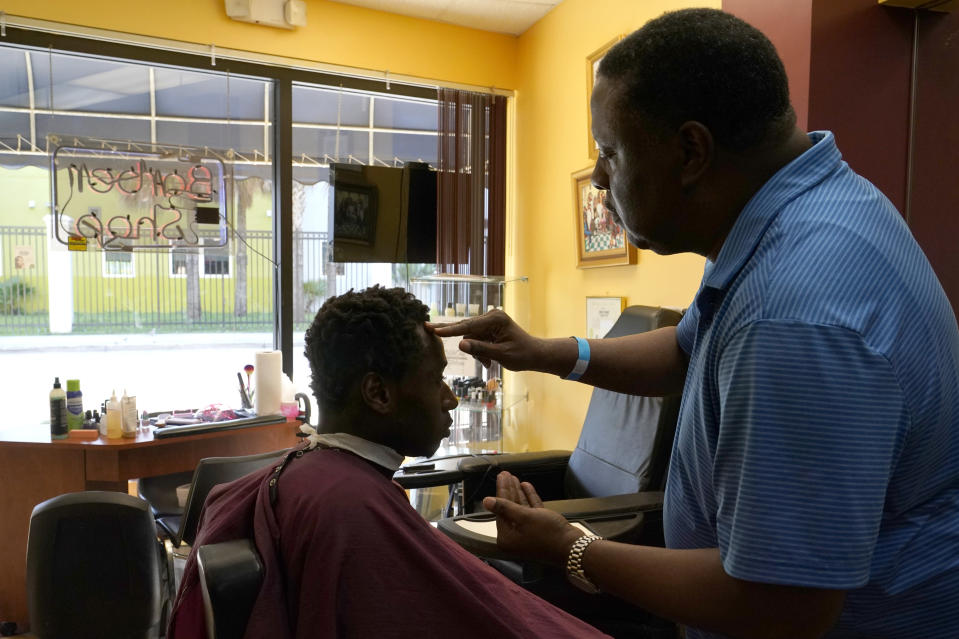 Willie Williams, right, owner of the Just Right Barber Shop, cuts the hair of Jeremiah Crossley, Friday, May 14, 2021, in the Overtown neighborhood in Miami. Just Right has been in the Overtown community as a family business for over 70 years. (AP Photo/Lynne Sladky)