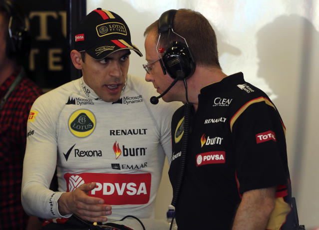 Lotus driver Pastor Maldonado, left, of Venezuela chats with a technician in his garage during the first practice session for the Australian Formula One Grand Prix at Albert Park in Melbourne, Australia, Friday, March 14, 2014. (AP Photo/Rob Griffith)