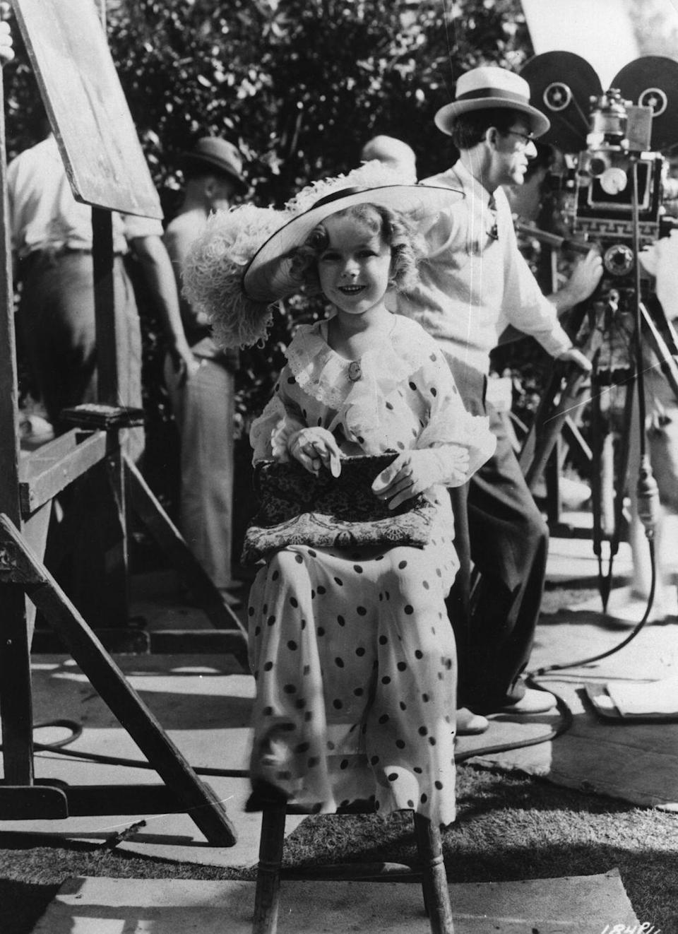 <p>Eight-year-old child actress, Shirley Temple, takes a break during a busy day of filming. The actress starred in films like <em>Heidi </em>and <em>The Little Princess </em>throughout out her career and started in the industry at the age of three. </p>