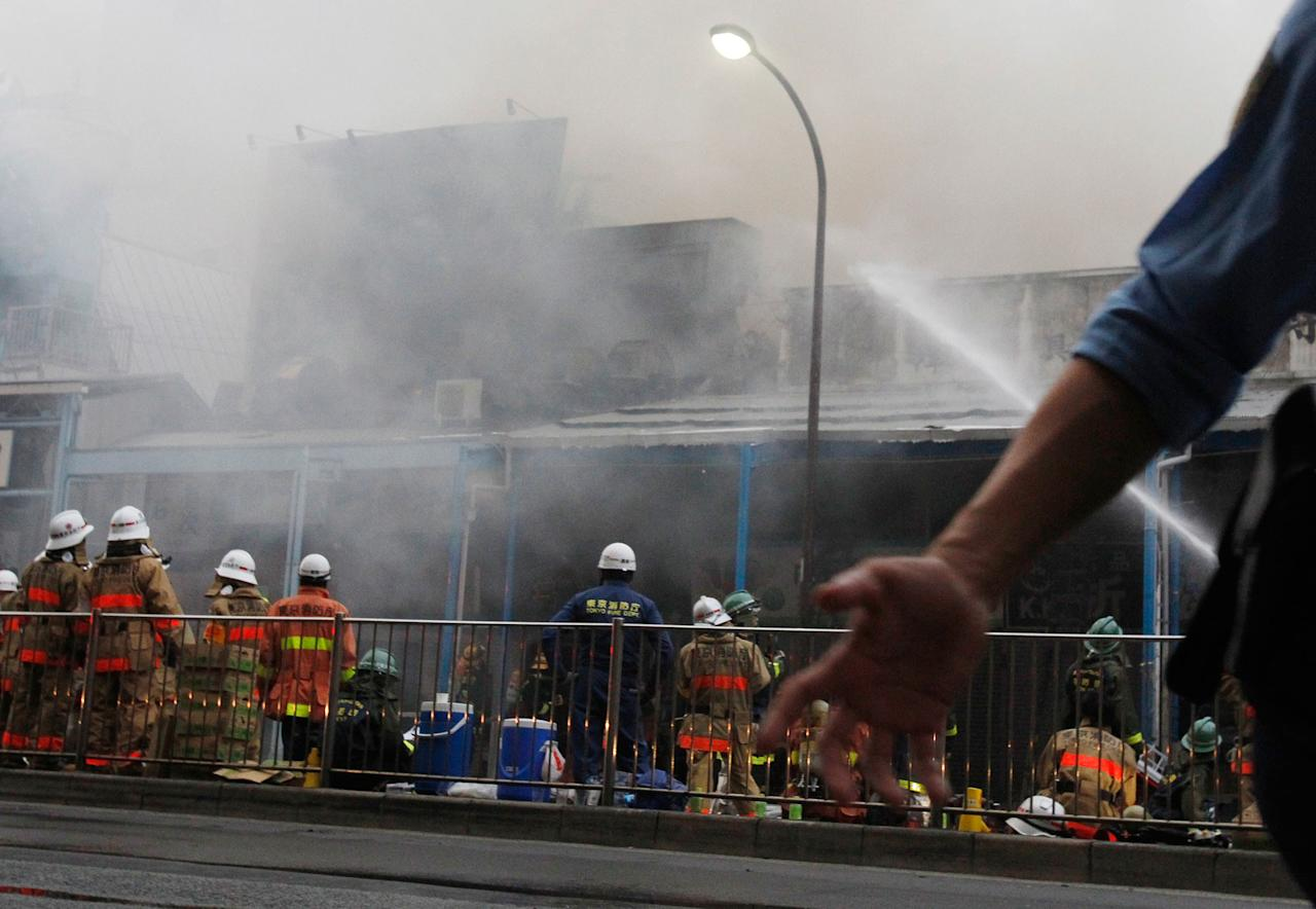 <p>Police manage crowds as firefighters work to extinguish the fire at Tsukiji Fish Market on Thursday, Aug. 3, 2017, in Tokyo. (Photo: Sherry Zheng/AP) </p>