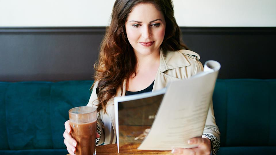 Shot of a young woman reading a magazine in a cafe.