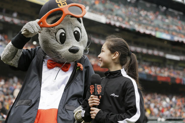 "Alysa Liu, right, the 13-year-old U.S. figure skating national champion, smiles at San Francisco Giants mascot Lou Seal, before yelling ""Play ball!,"" before a baseball game between the San Francisco Giants and the Tampa Bay Rays, Friday, April 5, 2019, in San Francisco. (AP Photo/Eric Risberg)"