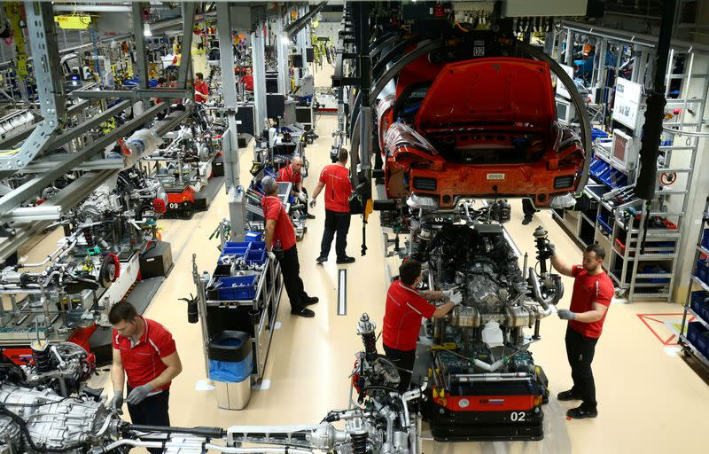 FILE PHOTO: Employees of German car manufacturer Porsche assemble sports cars at the Porsche factory in Stuttgart-Zuffenhausen