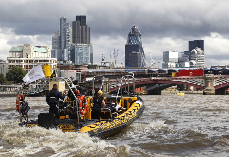 In this Wednesday, July 4, 2012, a high-speed 12-seater rigid inflatable boat, run by the Protection Services International company, travels past London's financial district. Companies like Protection Services International are just one of the many catering to the super rich who are coming to the London games and demand top security and easy transport. (AP Photo/Lefteris Pitarakis)