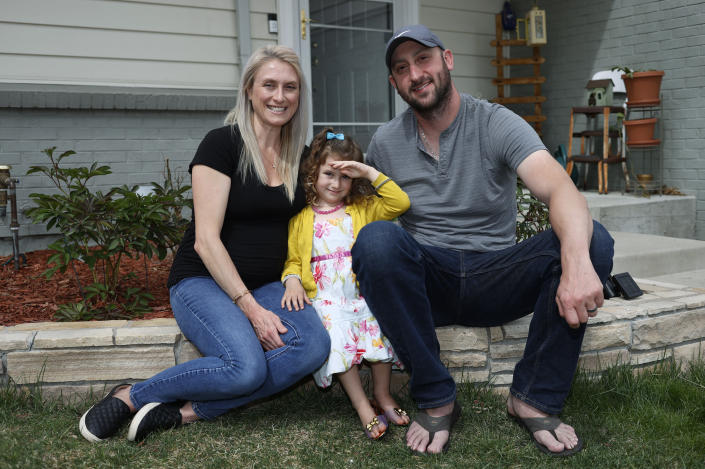 FILE - In this April 30, 2020, file photo, Eli Oderberg, right, sits with Katie Evers and their 4-year-old daughter, Everlee, outside their home in southeast Denver. Oderberg lost his job in a wave of layoffs in April, and he remains unemployed as he and his wife fear running out of money once their new baby arrives. They are among millions of Americans struggling to pay bills as the coronavirus pandemic continues. (AP Photo/David Zalubowski, File)