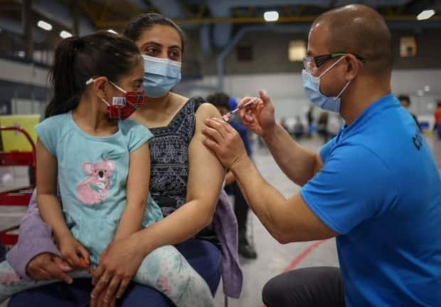 Five-year-old Raavi Mahal watches her mom, Loveleen Mahal, receive the COVID-19 vaccine from Dr. Oliver Haw. (Alberta Health Services - image credit)