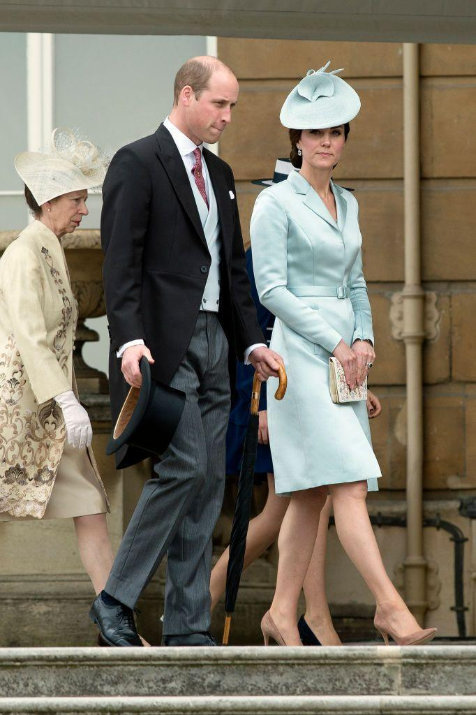 <p>For the first garden party of the season, the Duke and Duchess coordinate their pastel looks. Prince William wore a silk blue vest to match the Duchess's satin blue Chistopher Kane suit dress. She topped off the outfit with a fascinator from John Locke & Co. </p>