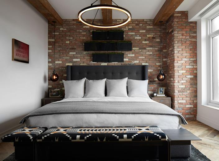"""One of the elements Kevin was dead set on bringing in to the bedroom was this reclaimed brick,"" says Varnum. ""He has something similar in a basement bar in his home in Cleveland."" The bed is custom by Wodarczyk Interiors Workroom, and the linens are custom as well, by Block Brothers. A Desiron bench was covered in Pendleton's Spider Rock throw material. The overhead light is by Restoration Hardware. Love was also interested in bringing in some greenery, some nature into the bedroom, so Varnum introduced a low-maintenance living moss garden above his headboard."