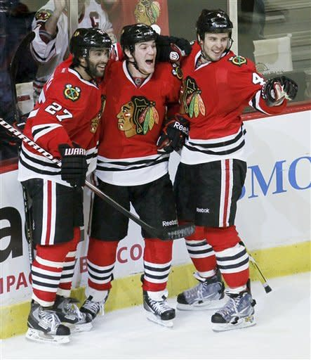 Chicago Blackhawks' Andrew Shaw, center, celebrates his game-winning overtime goal with Johnny Oduya (27) and Niklas Hjalmarsson (4) that gave the Blackhawks a 2-1 win over the Vancouver Canucks in an NHL hockey game in Chicago, Wednesday, March 21, 2012. (AP Photo/Charles Rex Arbogast)