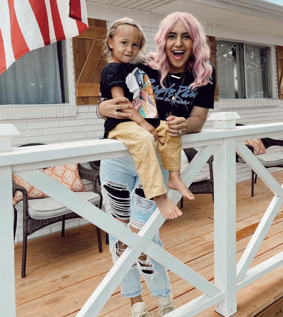 The dance teacher is seen with one of her five children while wearing a pink wig.