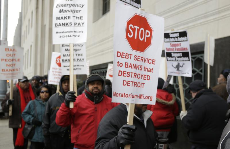 Detroit city workers and supporters protest outside the federal courthouse in Detroit while awaiting the bankruptcy decision, Tuesday, Dec. 3, 2013. A judge on Tuesday ruled that the city of Detroit can cut pensions as a way out of the largest municipal bankruptcy in U.S. history. (AP Photo/Carlos Osorio)