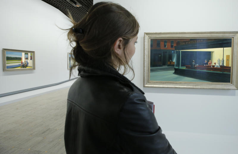 """A woman looks at """"Nighthawks, 1942"""", at right, as part of the retrospective of Edward Hopper, one of the great American 20th century artists at Paris' Grand Palais Museum, in Paris, Monday, Oct. 8, 2012. This major Hopper retrospective reveals that the 20th century painter known for his rendering of American life, also drew inspiration from France, and includes some 128 Hopper works, such as the masterpieces """"Nighthawks"""" and """"Soir Bleu"""".(AP Photo/Francois Mori)"""