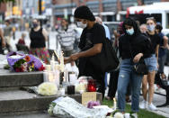 <p>A mourner lights a candle at a memorial for the four family members who were killed in a vehicle attack that police say was motivated by anti-Muslim hate, in London, Ont., in Ottawa, on Tuesday, June 8, 2021. THE CANADIAN PRESS/Justin Tang</p>