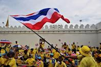 Royal devotion was on display as thousands of supporters, some waving flags, waited for the King and Queen near the Grand Palace