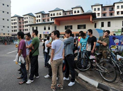 Foreign workers wait for their transportation to work outside their dormitory in Singapore on November 26