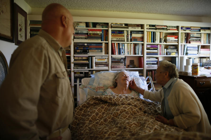 Constantine Moundalexis, 55, (L) watches as a Meals on Wheels volunteer greets his house-bound mother, Catherine Morgan, 82, in Sun City, Arizona, January 5, 2013. Moundalexis moved next door to his mother to take care of her during the final stage of her life. Sun City was built in 1959 by entrepreneur Del Webb as America's first active retirement community for the over-55's. Del Webb predicted that retirees would flock to a community where they were given more than just a house with a rocking chair in which to sit and wait to die. Today's residents keep their minds and bodies active by socializing at over 120 clubs with activities such as square dancing, ceramics, roller skating, computers, cheerleading, racquetball and yoga. There are 38,500 residents in the community with an average age 72.4 years. Picture taken January 5, 2013. REUTERS/Lucy Nicholson (UNITED STATES - Tags: SOCIETY) ATTENTION EDITORS - PICTURE 22 OF 30 FOR PACKAGE 'THE SPORTY SENIORS OF SUN CITY' SEARCH 'SUN CITY' FOR ALL IMAGES