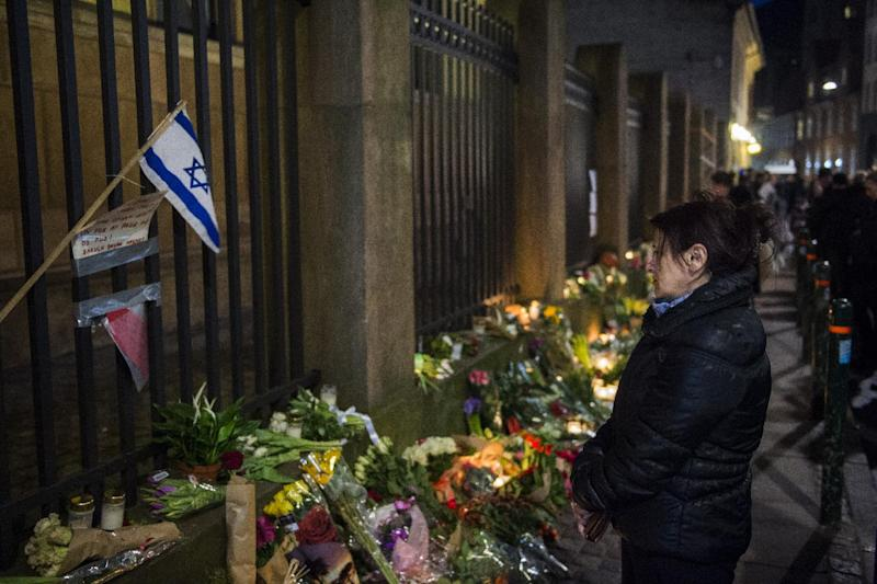 Well-wishers bring flowers and light candles to honour the shooting victims outside the main synagogue in Copenhagen, on February 15, 2015