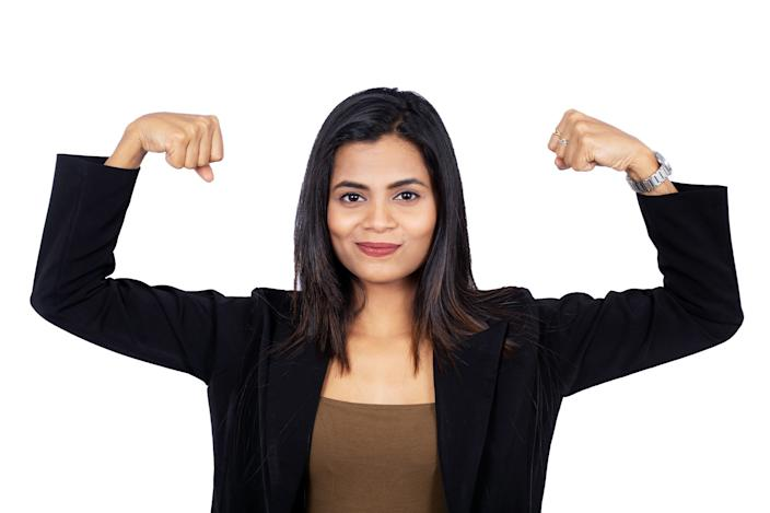 Portrait of confident Indian businesswoman flexing her muscles to show her girl power. Beautiful female professional is over white background. She is wearing elegant suit.