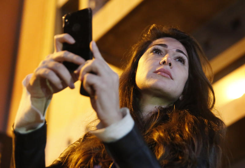 In this Wednesday, Dec. 4, 2019 photo, Lebanese anchorwoman Dima Sadek uses her cellphone to film an anti-government protest, in Beirut, Lebanon. Sadek, who last month resigned as an anchorwoman at the LBC TV, blamed Hezbollah supporters for robbing her smartphone while she was filming protests, and said the harassment was followed by insulting and threatening phone calls to her mother, who suffered a stroke as a result of the stress. (AP Photo/Hussein Malla)