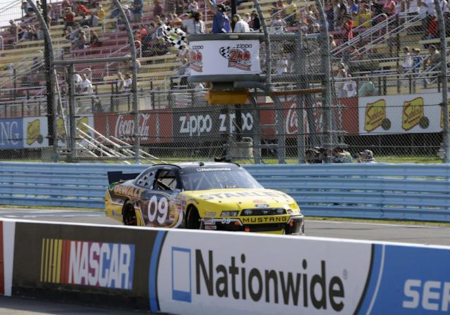 Marcos Ambrose (09) takes the checkered flag to win a NASCAR Nationwide Series auto race at Watkins Glen International, Saturday, Aug. 9, 2014, in Watkins Glen N.Y. (AP Photo/Mel Evans)