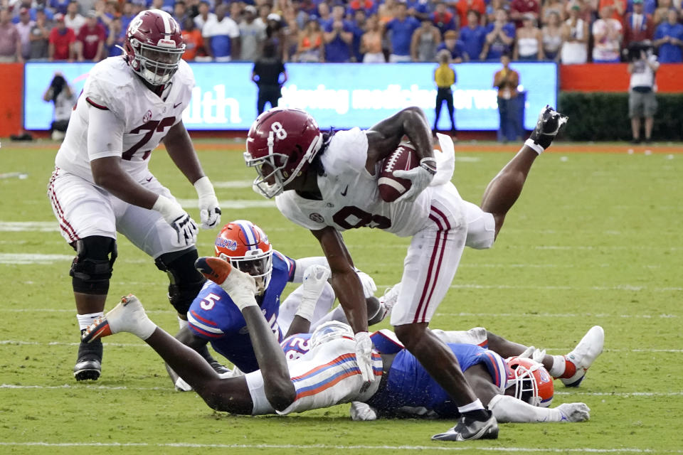 Alabama wide receiver John Metchie III (8) hurdles past Florida defensive players cornerback Kaiir Elam (5), linebacker Ty'Ron Hopper and safety Trey Dean III during the second half of an NCAA college football game, Saturday, Sept. 18, 2021, in Gainesville, Fla. (AP Photo/John Raoux)
