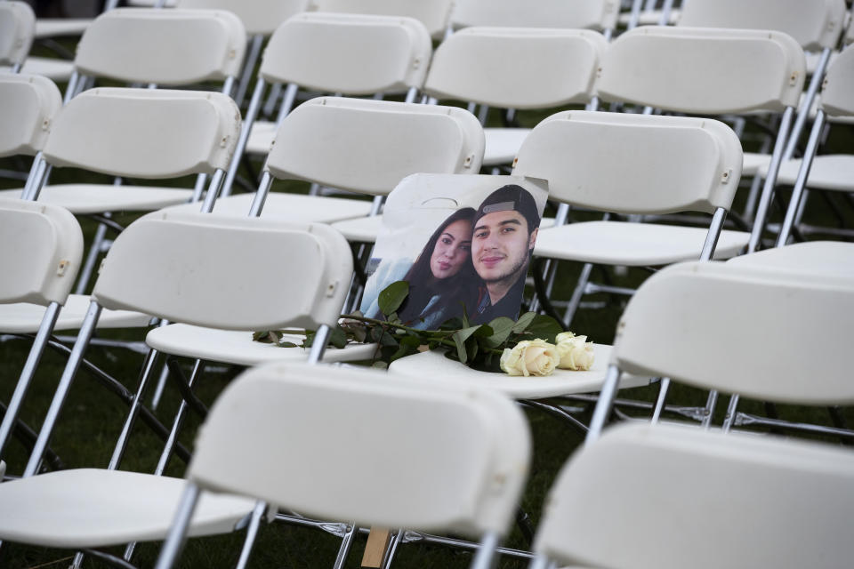 FILE- In this Sunday, March 8, 2020, file photo, A picture of Bryce Fredriksz and his girlfriend Daisy is placed amidst 298 empty chairs, each chair for one of the 298 victims of the downed Malaysia Air flight MH17, in a park opposite the Russian embassy in The Hague, Netherlands. The trial in absentia in a Dutch courtroom of three Russians and a Ukrainian charged in the downing of Malaysia Airlines flight MH17 in 2014 moves to the merits phase, when judges and lawyers begin assessing evidence. (AP Photo/Peter Dejong, File)