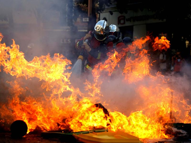 Firefighters extinguish a barricade during a protest over climate change in Paris: REUTERS