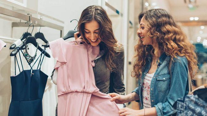 Two young women choosing dresses in a luxury fashion store.