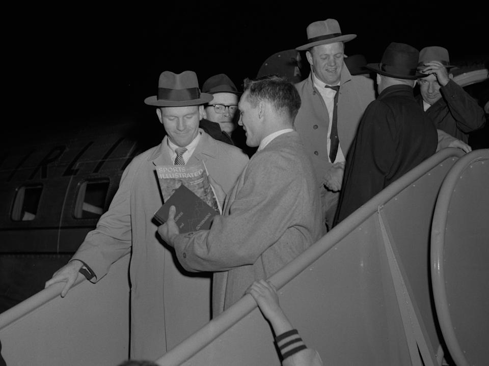 """Notre Dame player Dick Lynch, right, who scored the winning touchdown in the game, is all smiles as he shows head coach Terry Brennan a magazine article titled: """"Why Oklahoma is Unbeatable"""" as the team arrives back in South Bend on Nov. 16, 1957 after defeating the Sooners 7-0.South Bend Tribune Archives"""