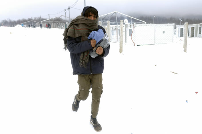 A migrant carries footwear and blankets received from humanitarian organization at the Lipa camp, outside Bihac, Bosnia, Monday, Jan. 11, 2021. Aid workers say migrants staying at a camp in northwestern Bosnia have complained or respiratory and skin diseases after spending days in make-shift tents and containers amid freezing weather and snow blizzards. Most of the hundreds of migrants at the Lipa facility near Bosnia's border with Croatia on Monday have been accommodated in heated military tents following days of uncertainty after a fire gutted most of the camp on Dec. 23. (AP Photo/Kemal Softic)