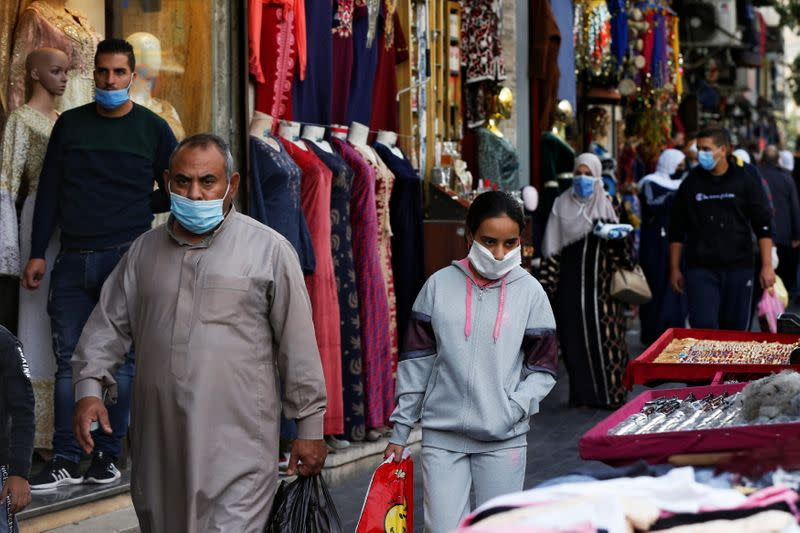 FILE PHOTO: People wearing protective masks walk in downtown Amman, amid fears over the rising number of the coronavirus disease (COVID-19) cases