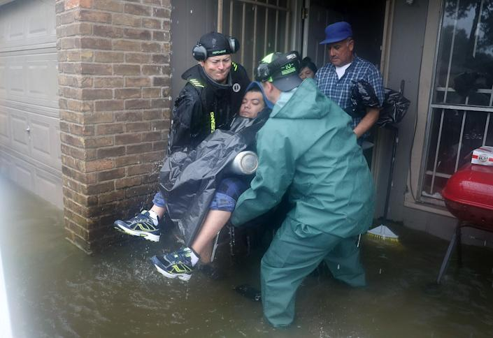 Dean Mize (left) and Jason Legnon carry a person to an airboat as they rescue people from their homes in Houston.