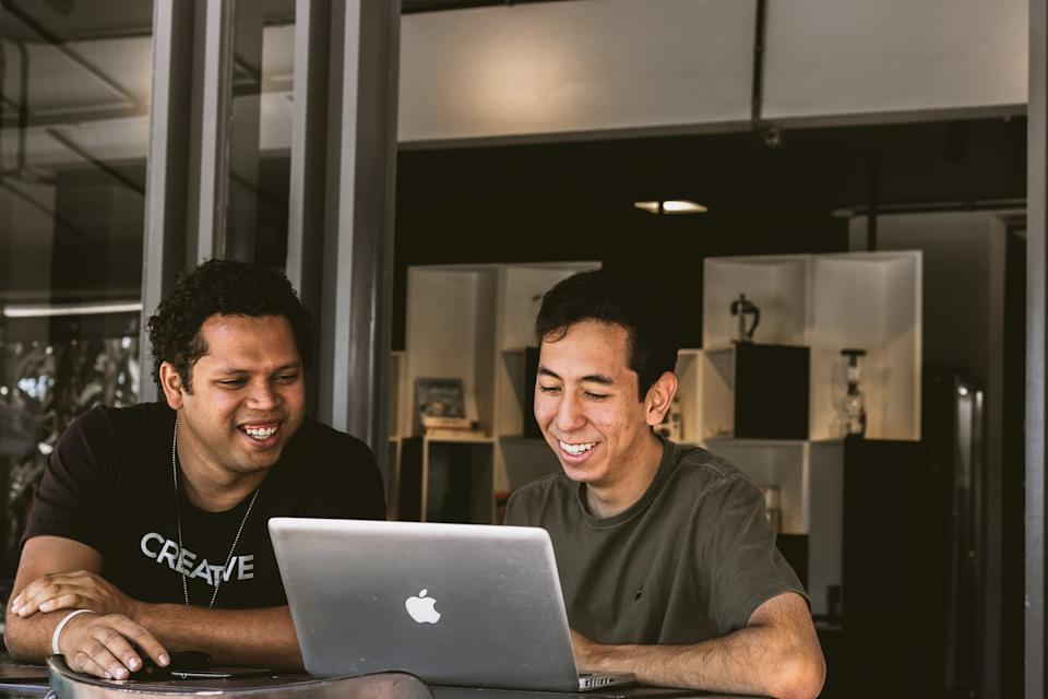 Two men sit looking at a laptop.