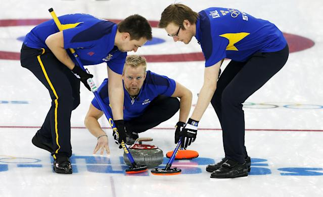 Sweden's skip Niklas Edin, center watches the rock while Fredrik Linberg, left, and Sebastian Kraupp, right, sweep the ice during the men's curling match against Russia at the 2014 Winter Olympics, Sunday, Feb. 16, 2014, in Sochi, Russia. (AP Photo/Wong Maye-E)