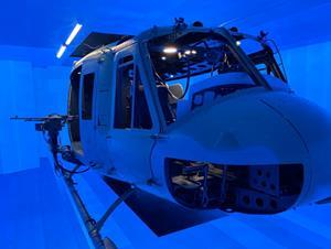 An actual UH-1 helicopter inside the blue electroluminescent interior of the Kratos immersive environment.